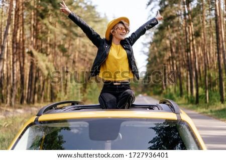 Happy Woman Sitting on Car Sunroof Freedom Concept. Road Trip Joy. Hipster Beautiful Caucasian Girl with Raised Arms on Yellow Vehicle Roof. Wanderlust Adventure at Summer Weekend. Carefree Lifestyle Foto stock ©