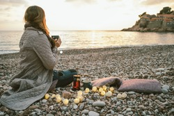 Happy woman sitting on cold beach with cup of tea with lights at sunset, Montenegro