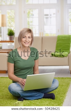 Happy woman sitting on floor at home in living room using laptop computer, looking at camera.