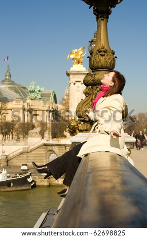 Happy woman sitting on the balustrade of the Pont Alexandre III in Paris