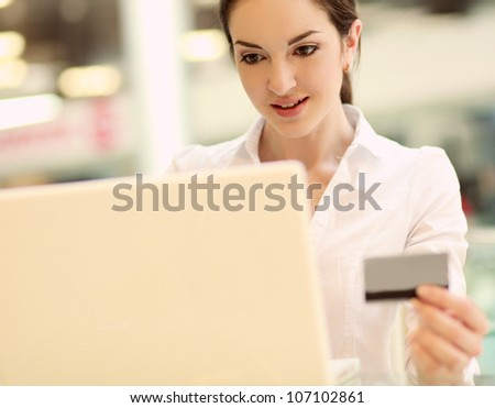 Happy woman sitting on the desk and shopping online isolated on white background