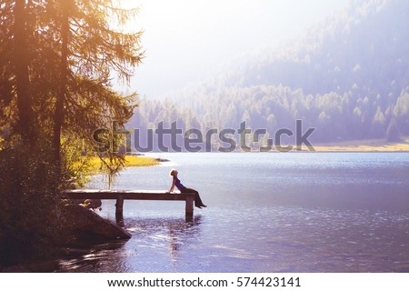 happy woman sitting on the pier and smiling, happiness or inspiration concept, enjoy life #574423141