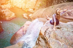 Happy woman sitting on the rock edge near waterfall enjoying stunning view, filtered with sun flares