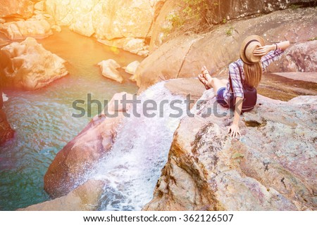 Happy woman sitting on the rock edge near waterfall enjoying stunning view, filtered with sun flares stock photo