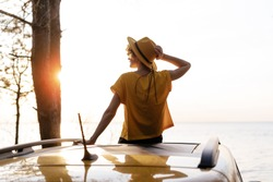 Happy Woman Sitting on Yellow Car Roof at Sunset. Back View of Young Girl on Automobile Rooftop Enjoy Summer Travel to Sea. Female Traveler Wearing Hat Relaxing during Road Trip