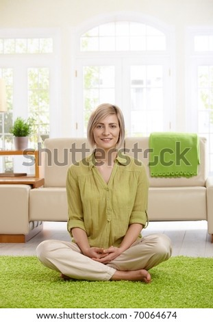 Happy  woman sitting with legs crossed on living room floor, looking at camera.?