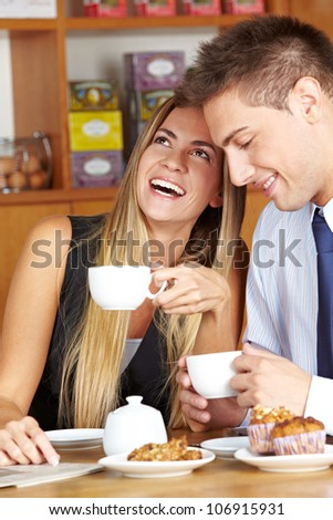 Happy woman sitting with man in caf�© drinking a cup of coffee