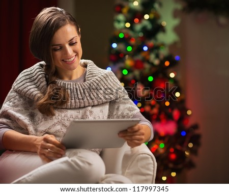 Happy woman sitting with tablet PC in front of Christmas tree