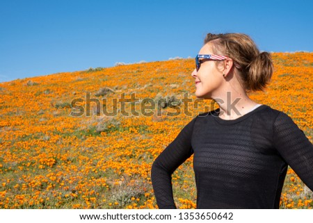 Happy woman smiles off into the distance looking at the bright orange hills filled with poppies during the superbloom at Antelope Valley Poppy Reserve in California
