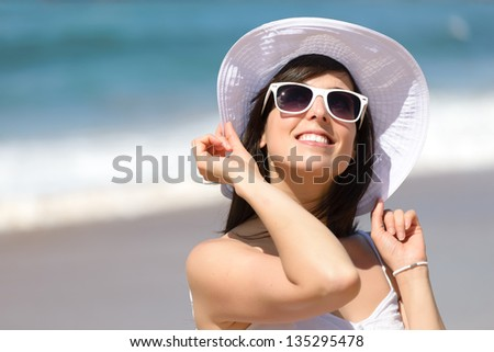 Happy woman smiling and enjoying on summer beach vacation. Beautiful caucasian girl in holidays, wearing white sunglasses and hat on sea background. Copy space.