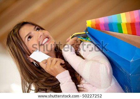 happy woman smiling with shopping bags and holding a credit card in a mall