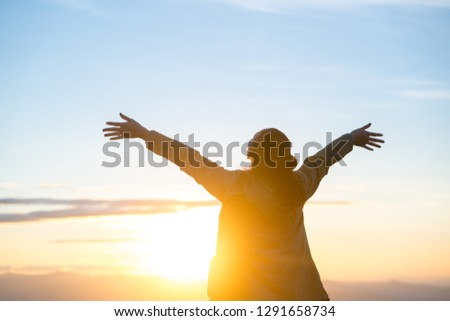 Happy woman standing alone with arms raised up during beautiful sunrise at the morning. #1291658734