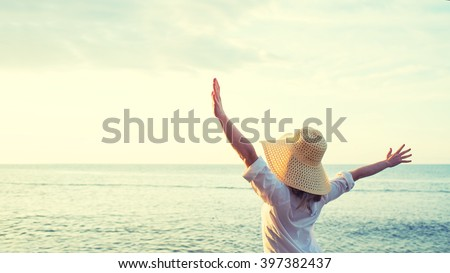 Happy woman standing arms outstretched back and enjoy life on the beach at Sea #397382437