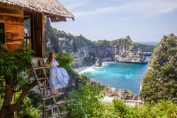 Happy woman standing near tree house at viewpoint Thousand Island. Travel destination in Bali, Indonesia. Popular place to visit on Nusa Penida island.