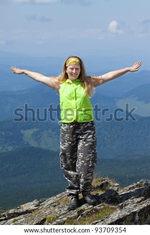 happy woman standing on  rock with raised hands  at mountain peak