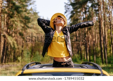 Happy Woman Standing out of Yellow Car Sunroof. Smiling Girl Stretching herself Enjoying Sunshine Front View. Beautiful Caucasian Model in Leather Jacket, Sunglasses and Hat on Auto Roof Foto stock ©