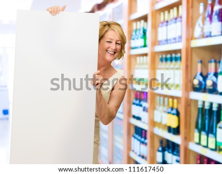 Happy Woman Standing With Blank Board By Shelves In Store
