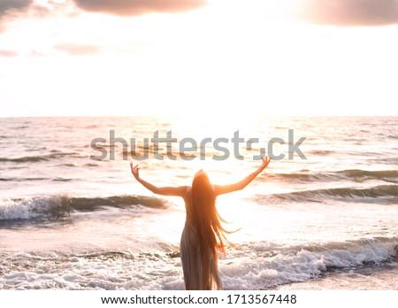 happy woman stands seashore turned away hand raised to heaven sky sun light. Lady girl enjoy sunny sunset sea waves. Concept hope divine pray freedom. Brunette long hair fluttering fly wind. Georgia Stock fotó ©