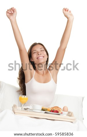 Happy woman stretching in bed in the morning with breakfast tray. Asian / Caucasian woman on white background.