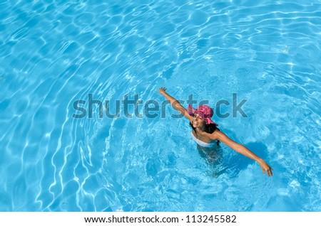 Happy woman swimming in pool on summer holidays. Brunette caucasian model playing into clear water on summer vacation. Copyspace.