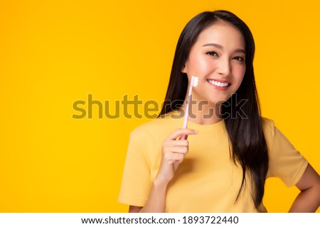 Happy woman take care tooth and holding toothbrush Young lady brushing her teeth Beautiful asian girl has beautiful tooth, white teeth   nice tooth alignment Yellow background, copy space Dental care