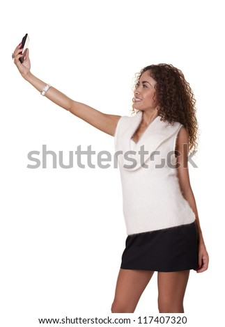 Happy woman takes a picture of herself with her phone, isolated on a white background.