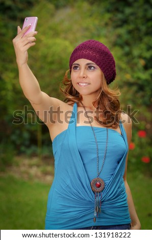 Happy woman takes a picture of herself with her phone, outdoors