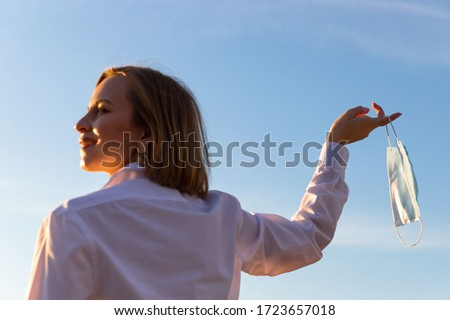 Happy woman takes off medical protective mask holds it on her finger on blue sky background, enjoys life, clean fresh air after Covid-19 pandemic, self-isolation. Quarantine is over. Soft focus