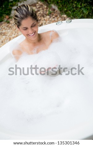 Happy woman taking a bath in a hot tub