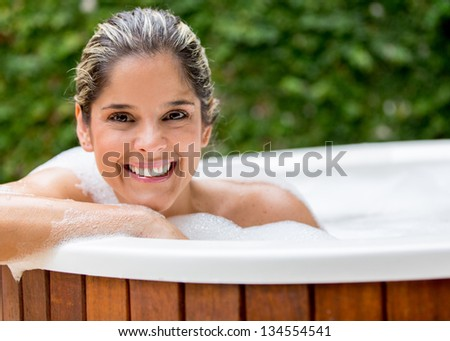 Happy woman taking a bath in the hot tub