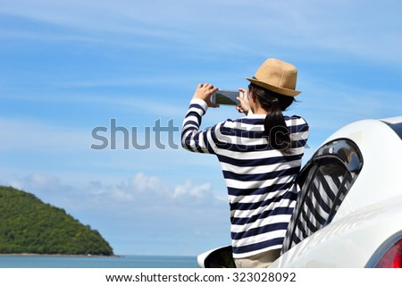 Happy woman taking photos to the sea with smartphone camera on car