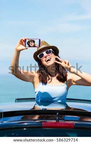 Happy woman taking smartphone selfie photo on car summer travel vacation to the coast. Brunette girl  leaning out car sunroof with the sea on background.