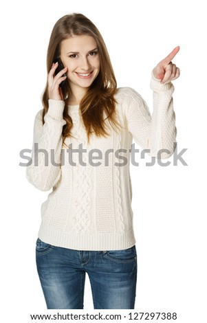Happy woman talking on cell phone and pointing to the side, over white background