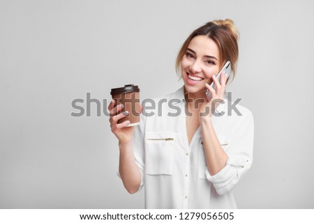 Happy woman talking on phone and drinking coffee, grey background