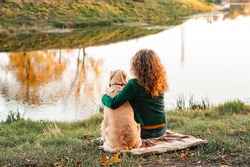 Happy woman together with golden retriever dog in a park outdoors. Young female owner hugging pet in park on brown blanket plaid. love and care for the pet. Back view