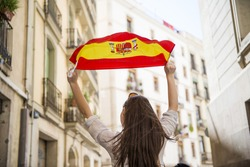 Happy woman tourist is walking in the city street of Barcelona with spanish flag.