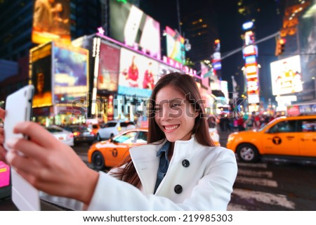 Happy woman tourist taking photo picture with tablet in New York City, Manhattan, Times Square. Girl traveler taking selfie joyful and happy smiling. Multiethnic Asian Caucasian woman in her 20s.