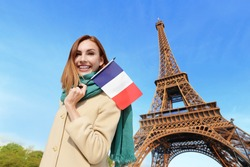 Happy woman travel in Paris with eiffel tower and beautiful blue sky and holding France French flag, caucasian beauty