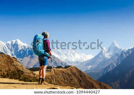 Happy Woman Traveler with Backpack hiking in Mountains with beautiful Himalaya landscape on background. Everest base camp trek #1094440427