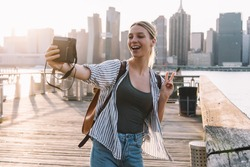 Happy woman traveller with retro technology having fun during vacations in United States showing v-sign while clicking selfie picture with Manhattan district on background, recreating journey