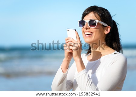 Happy woman typing chat message on cell phone. Brunette girl reading or writing sms on her mobile smartphone.