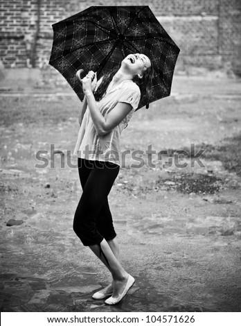 Happy woman under rain with umbrella