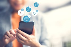 Happy woman using a social media marketing concept on mobile smartphone with notification icons of love, like, message, comment and email.