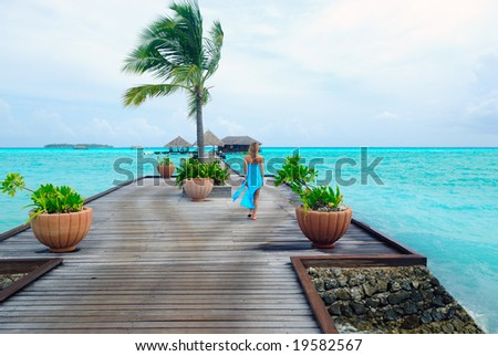 happy woman walking on the tropical beach
