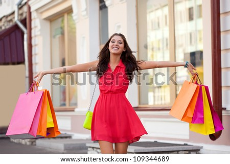happy woman walking with shopping bags