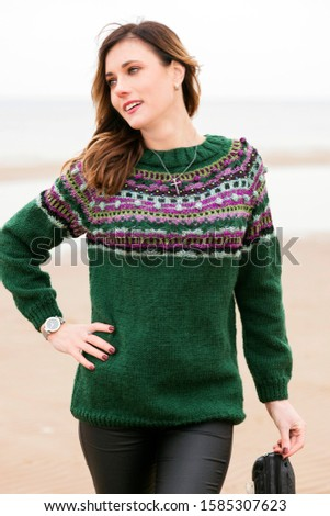 Happy woman walks along the winter beach in a knitted green sweater with an ornament