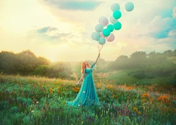 Happy woman walks in blooming valley. Fantasy girl princess holding in hand ball air balloon. long blue tulle fashion dress. Sunset sky, magic haze fog, flowers green meadow. blonde hair. Smiling face