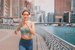 Happy woman wearing headphones and activewear top exercising and does running and fitness on the sidewalk of the embankment in the Dubai Marina area
