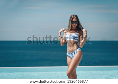 Happy woman wearing striped swimsuit and black sunglasses stands near pool during holidays summer time. Beautiful  blue seascape. Phuket. Thailand.