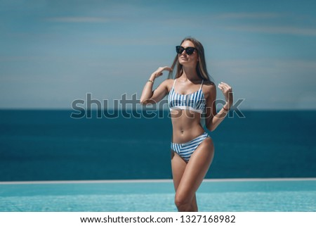 Happy woman wearing striped swimsuit and black sunglasses stands near pool during holidays summer time. Beautiful  blue seascape. Phuket. Thailand. Selective focus